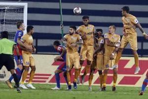 Mumbai City FC players, in yellow, react to stop the ball during the Hero Indian Super League (ISL) soccer match between Bengaluru FC and Mumbai City FC in Bangalore, India, Sunday, Dec. 9, 2018. (AP Photo/Aijaz Rahi)