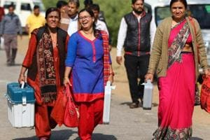 Election officials leave after collecting their Electronic Voting Machine (EVM) from an EVM distribution centre ahead of Rajasthan Assembly elections, at Bhawani Niketan in Jaipur
