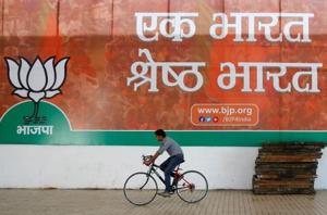 A worker of the Bharatiya Janata Party (BJP) rides his bicycle past the party