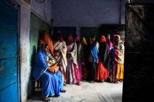 Women stand in queue to cast their vote at a local polling station during Rajasthan