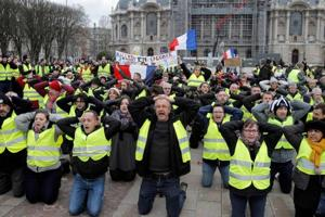 "Protestors wearing ""yellow vests"" (gilets jaunes) demonstrate on their knees against rising costs of living in Lille, northern France, on December 8, 2018.  The ""yellow vest"" movement in France originally started as a protest about planned fuel hikes but has morphed into a mass protest against President"