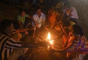 People sit around campfire on a winter evening in Pune.