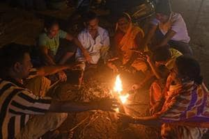 People sit around camp fire on a winter evening in Pune