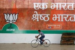 A worker of the BJP rides his bicycle past the party