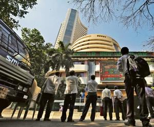 People look at a screen displaying the Sensex results on the facade of the BSE building in Mumbai.