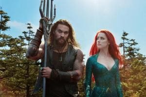 This image released by Warner Bros. Pictures shows Jason Momoa, left, and Amber Heard in a scene from Aquaman.