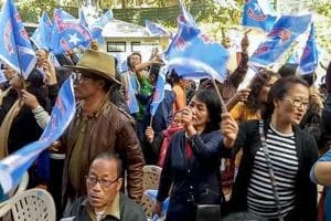 Mizo National Front (MNF) workers hold up party flag as they celebrate the party