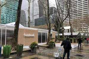 """People walk by a Facebook """"pop-up"""" trailer in New York's Bryan Park on Thursday, Dec. 13, 2018. The company hosted a one-day event open to the public, with Facebook employees on hand to answer questions about privacy settings and other issues. The pop-up event caps a difficult year for the company."""