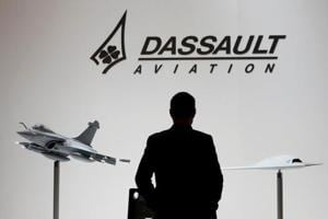 A visitor looks at replicas of the fighter jet Rafale (L) and Neuron on the Dassault booth during the European Business Aviation Convention & Exhibition (EBACE) at Cointrin airport in Geneva, Switzerland, in this picture taken on May 19.