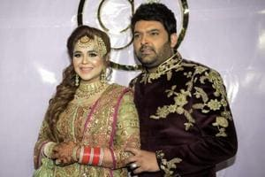 Kapil Sharma and his wife Ginni Chatrath pose during their wedding reception party at a hotel in Amritsar on December 14, 2018. (Photo by NARINDER NANU / AFP)