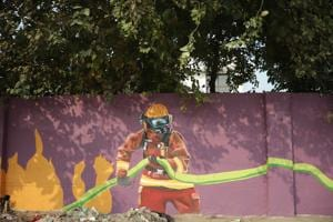 Valour of a fireman has been brought forth through his image in a fire suit in this street art. (HT Photo)