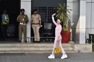 Alia Bhatt waves to fans outside the airport.