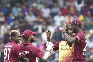 West Indies captain Carlos Brathwaite (right) celebrates with his teammates after the fall of a Bangladeshi wicket.