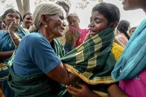A crying boy being consoled by his grandmother after his mother died of suspected food poisoning at Bidarahalli, near Sulawadi village in Chamarajnagar district of Karnataka state, on Saturday. Police on Saturday arrested three people after at least 10 died of suspected food poisoning following a ceremony to celebrate the construction of a new temple.