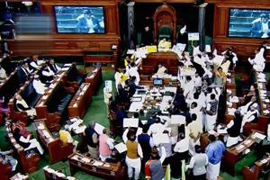 Members protest in the well of the Lok Sabha during the Winter Session of Parliament, in New Delhi