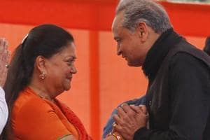 Outgoing Rajasthan chief minister Vasundhara Raje, center, greets new chief minister Ashok Gehlot during his swearing in ceremony at Jaipur.