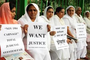 (FILES) In this file photo taken on October 31, 2006 relatives of Indian Sikhs killed in the 1984 riot hold placards during a protest demanding justice in New Delhi. - An Indian court on November 20, 2018 handed down first death penalty over deadly 1984 anti-Sikh riots. (Photo by RAVEENDRAN / AFP)
