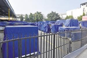 Large marble slabs wrapped in blue plastic sheets can be seen on both sides of the road in Chhattarpur.