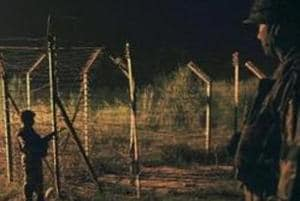 Soldiers standing guard during a night patrol near the fence at the India-Pakistan International Border at the outpost of Akhnoor sector.