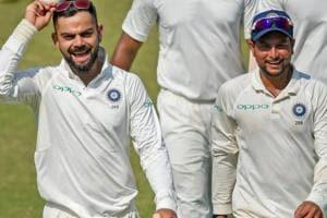 Virat Kohli and team player Kuldeep Yadav celebrate their victory in the first Test match, in Rajkot.