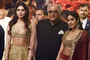 Boney Kapoor (C) with his daughters Khushi (L) and Janhvi Kapoor (R), attend the wedding of Isha Ambani with Anand Piramal in Mumbai. (Photo by - / AFP)