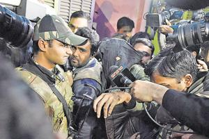 A boy arrested by the officials of National Investigation Agency during its raid, at Jaffrabad, Seelampur, in New Delhi, India, on Wednesday