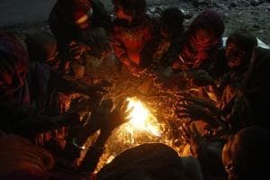 People sit near a bonfire to keep themselves warm on a cold winter evening, near Old Jail complex, in Gurugram
