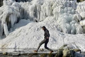 A man walks near the frozen water fall at Drung area of Tangmarg in Baramulla Distrct of North Kashmir