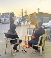 People enjoy the winter morning chill around a bornfire at the old Mumbai Highway on Saturday.
