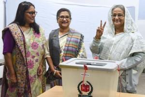 Bangladeshi Prime Minister Sheikh Hasina (R) flashes the victory symbol after casting her vote, as her daughter Saima Wazed Hossain (1st L) and her sister Sheikh Rehana (2nd L) look on at a polling station in Dhaka .