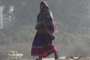 A woman wears warm clothes to protect herself from cold on a winter morning, at Okhla Railway Station, in New Delhi, India.
