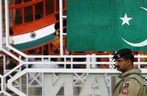 A Pakistani Ranger stands near the Pakistani flag and Indian flag.