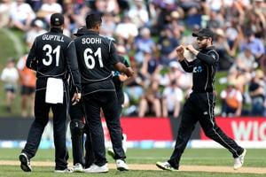 Kane Williamson (R), captain of New Zealand, and team-mate Ish Sodhi celebrate the dismissal of Josh Buttler of England during game four of the One Day International series between New Zealand and England at University of Otago Oval on March 7, 2018 in Dunedin, New Zealand.