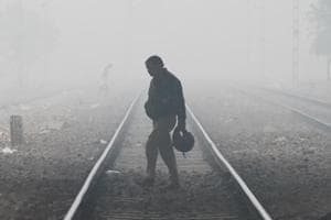 A man crosses railway track during morning hours amid fog at Delhi Cantt Railway Station, in New Delhi on January 3.