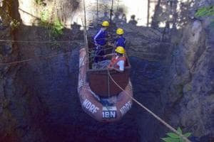 In this file photo taken on December 30, 2018 Indian Navy divers are lowered into a mine with a pulley during rescue operations to help 15 miners trapped by flooding in an illegal coal mine in Ksan village in Meghalaya