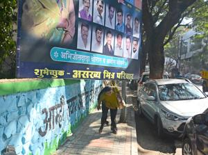 Pedestrians bend down to walk on a footpath as an illegal  hoarding encroached the footpath on Dhole Patil road.