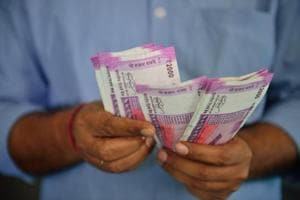 A man counts currency notes of Rs 2000.