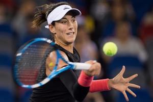 Garbine Muguruza of Spain hits a return against Katerina Siniakova of Czech Republic during their women