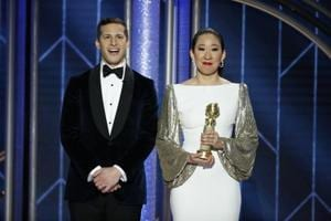 Host Sandra Oh holds her award for Best Actress - TV Series, Drama, Killing Eve while standing next to co-host Andy Samberg.