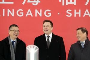 Robin Ren, vice president of sales at Tesla Inc., left, Elon Musk, chief executive officer, center, and Ying Yong, mayor of Shanghai, react during an event at the site of the company