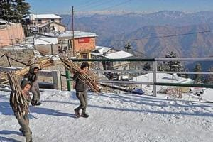 Children carrying wooden sticks home after snowfall at Kufri near Shimla on Monday. Many areas in Himachal Pradesh have been witnessing intermittent snow spell , snapping road and electricity connectivity across various regions.
