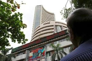 A man looks at a screen across a road displaying the Sensex on the facade of the Bombay Stock Exchange (BSE) building in Mumbai.