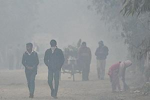 Commuters protect themselves from the cold at Akshardham on Tuesday morning.