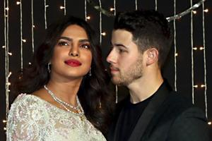 Bollywood actor Priyanka Chopra with husband-singer Nick Jonas pose for photos during their wedding reception, in Mumbai.