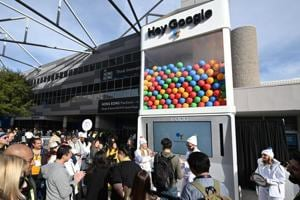 """Attendees wait in line to ask questions of Google Assistant at a giant """"Hey Google"""" gumball machine game at CES 2019."""