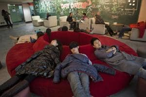 Staff members take a nap in the recreation room at the head office of Renren Inc. in Beijing, China. Photographer:Adam Dean/Bloomberg