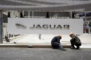 Workers set up the booth for British car manufacturer Jaguar Land Rover
