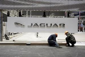 Workers set up the booth for British car manufacturer Jaguar Land Rover