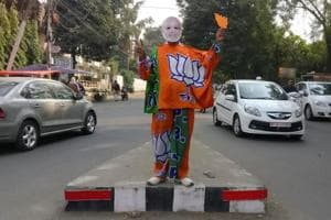 A supporter of Bharatiya Janata Party (BJP) wears a mask depicting Prime Minister Narendra Modi, and drapes himself with flags of BJP