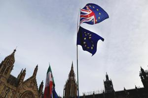 A Pro-European demonstrator raises flags to protest outside parliament in London, Friday, Jan. 11, 2019. Britain